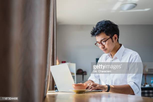 young asian business man working with laptop computer while sitting in coffee shop cafe - men stock pictures, royalty-free photos & images