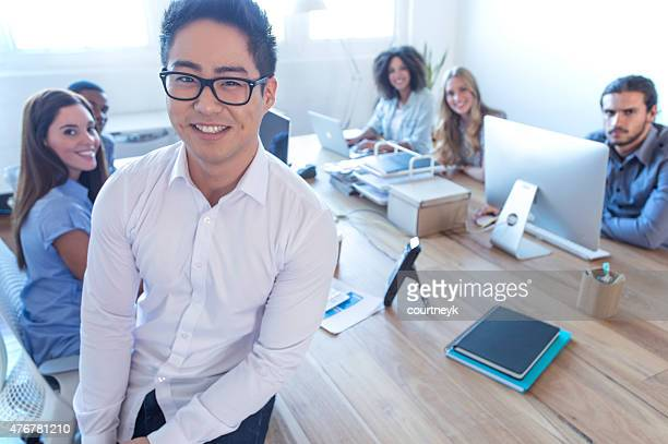 Young Asian business manager steht vor seinem team.