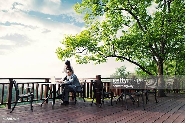 Jeunes gens d'affaires asiatique parlant au café en plein air