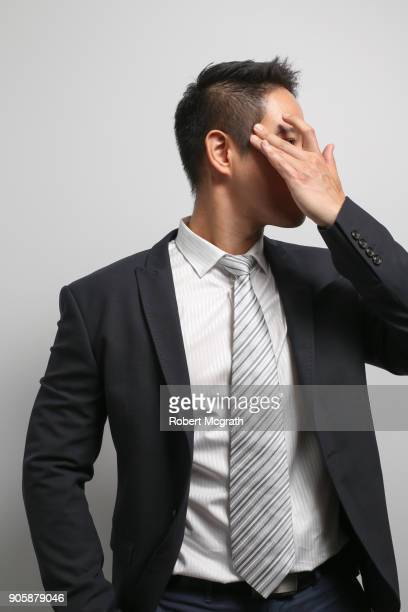 Young Asian business professional man lacquers his hair.