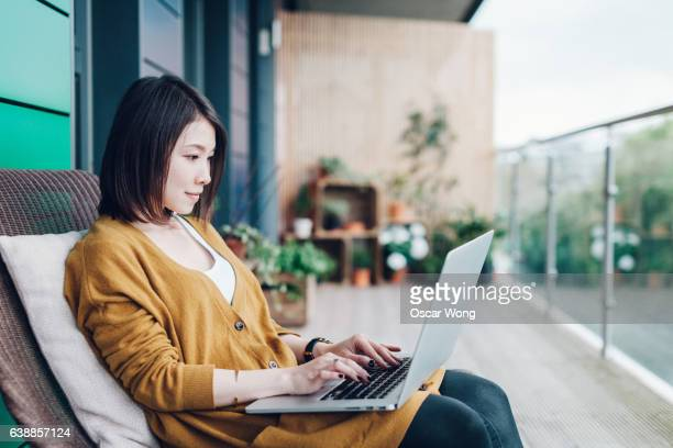 Young Asian business woman using laptop in balcony