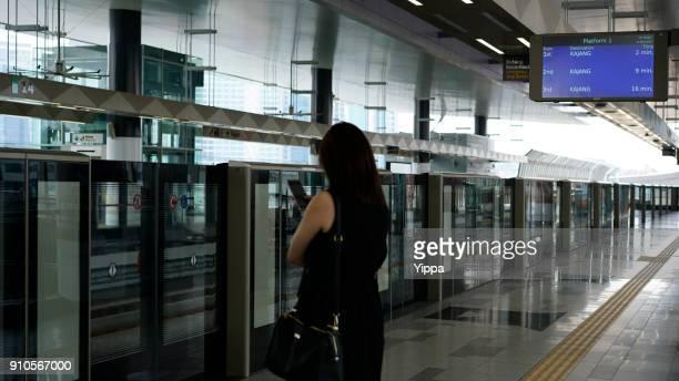 Young asian business women using phone in Kuala Lumpur MRT railway Station, Malaysia