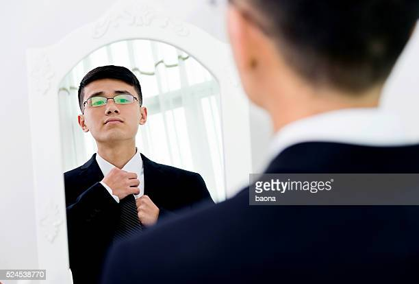 Young asian businessman adjusting necktie