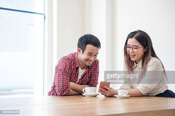 Young Asian businessman and businesswoman taking break with smartphone