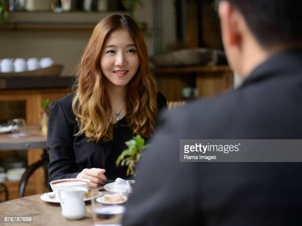 young asian businessman and young asian businesswoman relaxing together at the coffee shop - work romance stock pictures, royalty-free photos & images