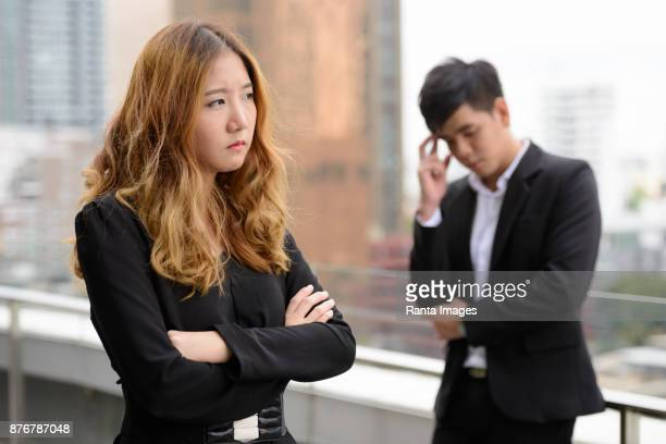 young asian businessman and young asian businesswoman together against view of the city - work romance stock pictures, royalty-free photos & images