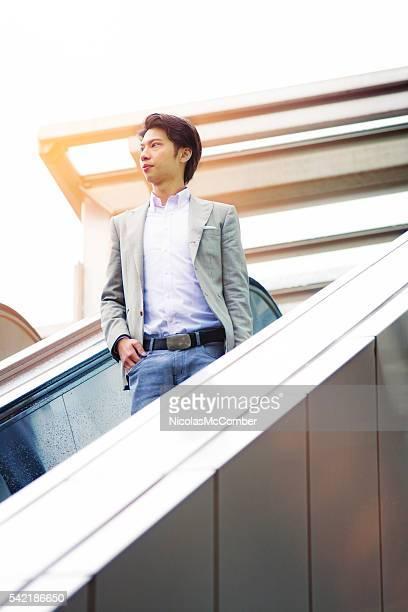 Young Asian businessman coming down outdoors  escalator