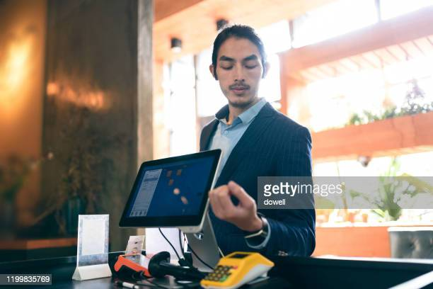 young asian businessman contactless payment with smart watch in restaurant - smart watch stock pictures, royalty-free photos & images