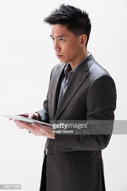 Young Asian businessman holding digital tablet, studio shot
