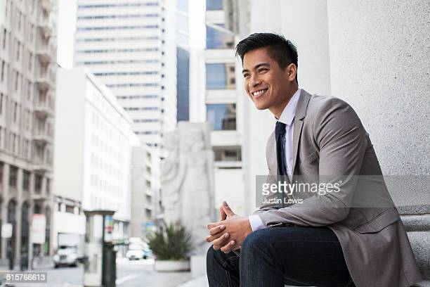 young Asian businessman in city smiling
