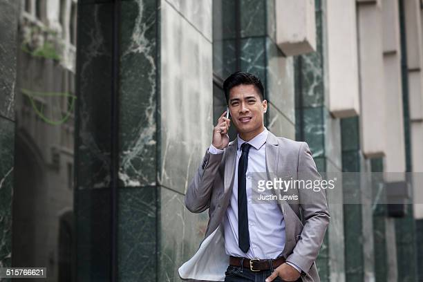 Young asian businessman on phone downtown