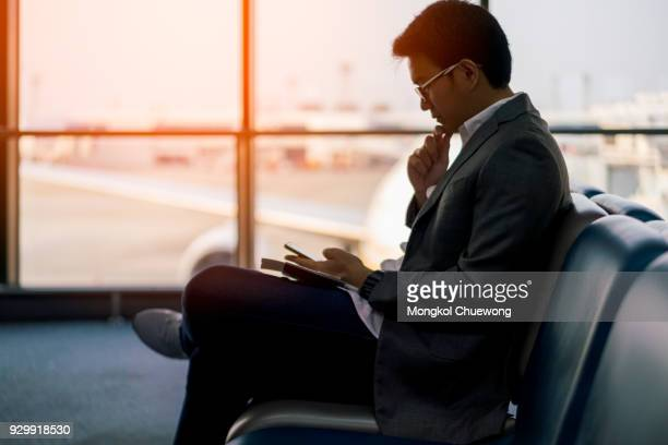 Young asian businessman sitting and using smartphone at waiting area in international airport