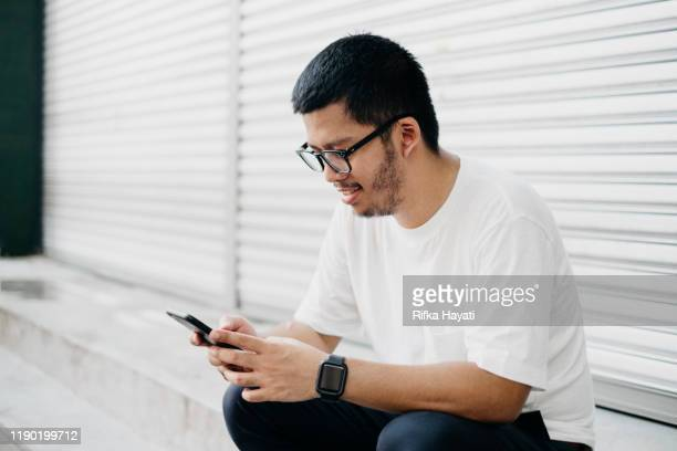 young asian businessman using smartphone - rifka hayati stock pictures, royalty-free photos & images