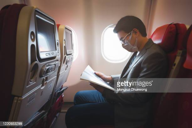 young asian businessman wearing protective face mask with suit sitting on airplane seat while reading magazine due to coronavirus or covid-19 outbreak situation in all of landmass in the world - image stock pictures, royalty-free photos & images