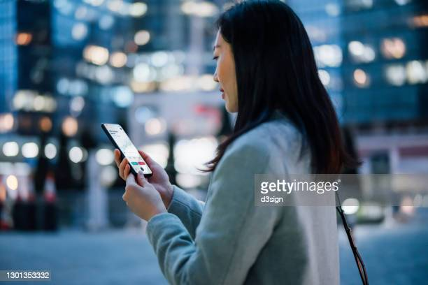 young asian businesswoman checking financial stock market analysis with mobile app on smartphone on the go, against illuminated contemporary corporate skyscrapers in financial district in the evening. business on the go - cryptocurrency stock pictures, royalty-free photos & images