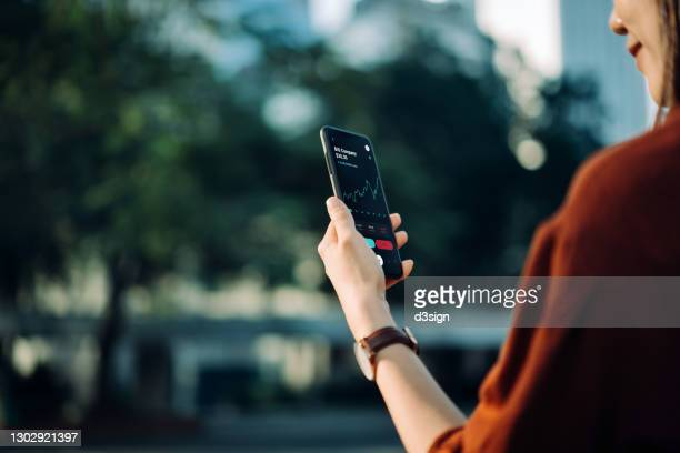 young asian businesswoman checking financial stock market analysis with mobile app on smartphone on the go in office park, against sunlight and nature green plants in central business district in the city. business on the go - blockchain stock pictures, royalty-free photos & images