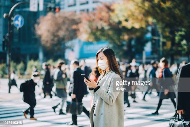 young asian businesswoman commuting in busy downtown city street with protective face mask and using smartphone to protect and prevent from the spread of viruses during covid-19 health crisis - business ストックフォトと画像