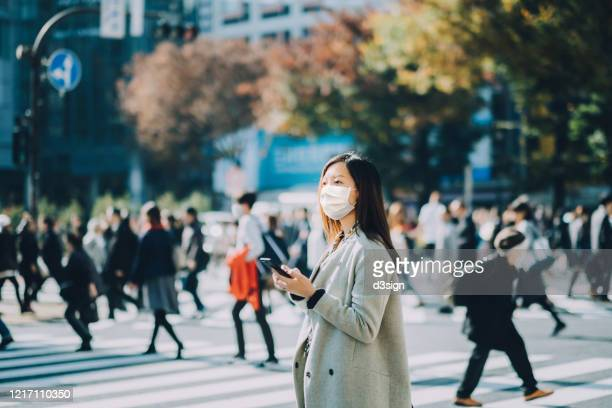 young asian businesswoman commuting in busy downtown city street with protective face mask and using smartphone to protect and prevent from the spread of viruses during covid-19 health crisis - covid-19 ストックフォトと画像
