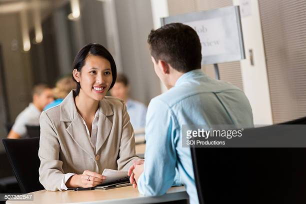 young asian businesswoman conducting interviews at job fair - job fair stock pictures, royalty-free photos & images