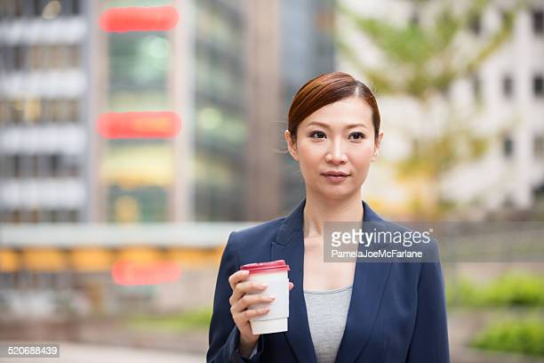 Young Asian Businesswoman Drinking Coffee Outside Office