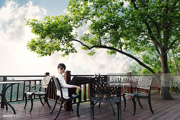 若いアジアビジネスウーマンの屋外カフェ」の座席
