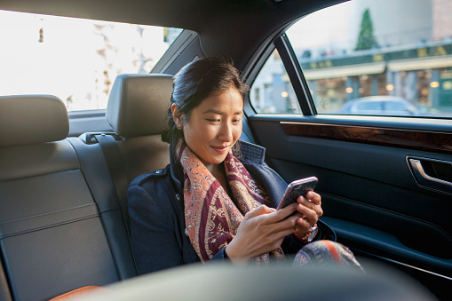 Young asian businesswoman looking at smartphone sitting in car service limousine - gettyimageskorea