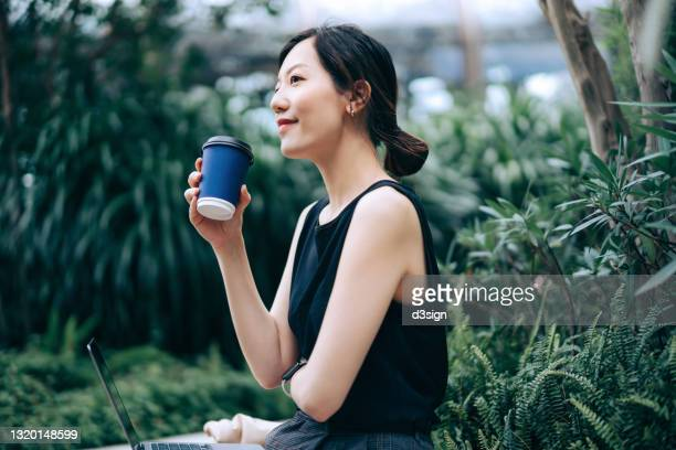 young asian businesswoman looking away while sitting on the bench in urban office park, surrounded by green plants. drinking a cup of coffee while working on laptop in the middle of a work day. outdoors with technology. remote working concept - coworking stock pictures, royalty-free photos & images