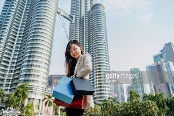 junge asiatische geschäftsfrau einkaufen nach der arbeit - kuala lumpur stock-fotos und bilder