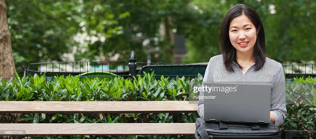young Asian businesswoman sitting on park bench working on laptop : Stock Photo