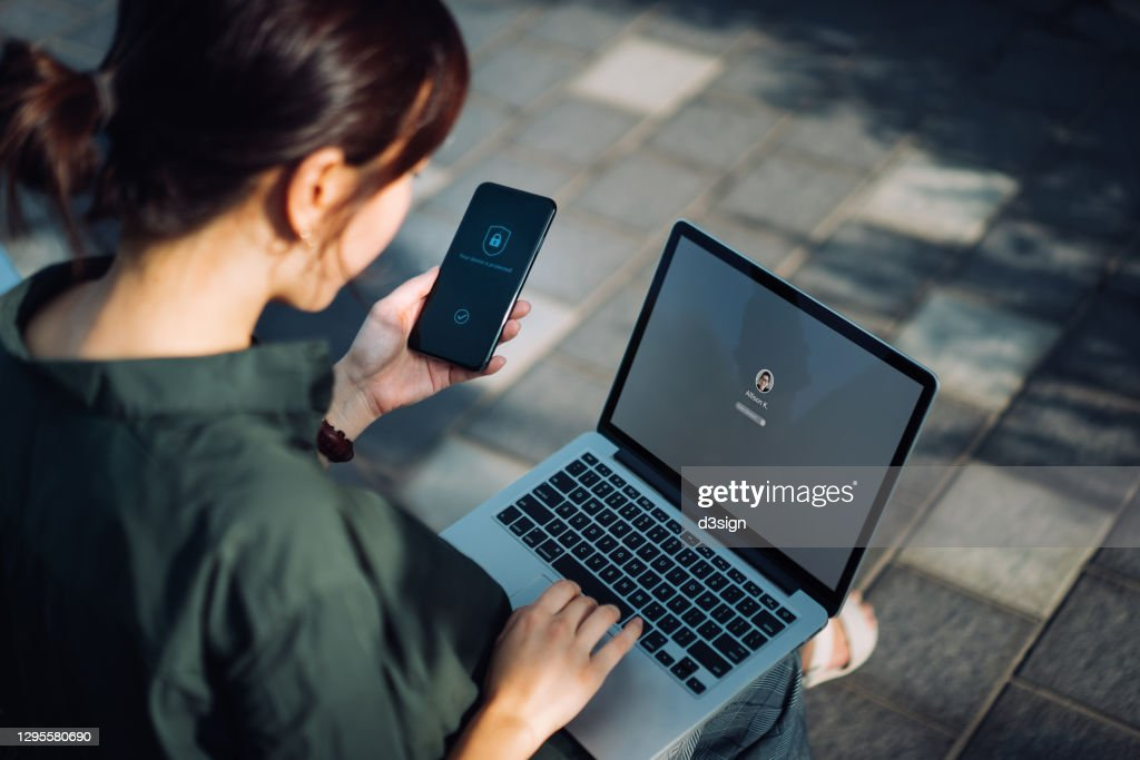 Young Asian businesswoman sitting on the bench in an urban park working outdoors, logging in to her laptop and holding smartphone on hand with a security key lock icon on the screen. Privacy protection, internet and mobile security concept : Stock Photo
