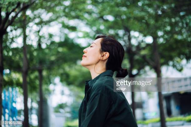 young asian businesswoman taking a break in urban park in the city. enjoying the gentle breeze with her eyes closed, resting in the middle of a work day - holy city stock pictures, royalty-free photos & images