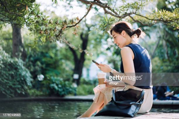 young asian businesswoman taking a coffee break in urban park in the city. she is sitting by the pond, using smartphone and enjoying a cup of coffee in the middle of a work day - smart watch stock pictures, royalty-free photos & images