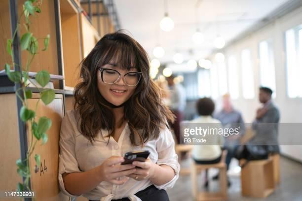 jonge aziatische zakenvrouw met mobiel op moderne cowerk ruimte - mobile stockfoto's en -beelden