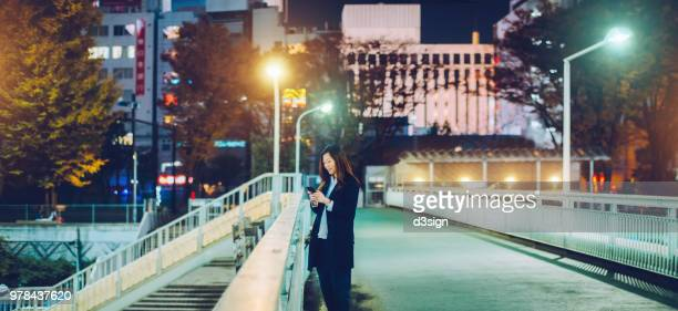 Young Asian businesswoman using mobile phone on urban bridge in city on the way home afterwork at night