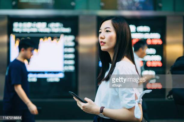young asian businesswoman using smartphone against stock exchange market display screen board in downtown financial district - bear market stock pictures, royalty-free photos & images