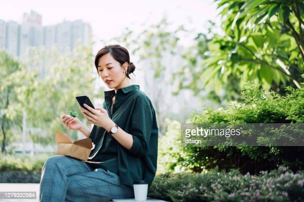 young asian businesswoman using smartphone while having a healthy salad lunch box outdoors in an urban park during lunch break, with a cup of coffee by her side - lunch stock pictures, royalty-free photos & images
