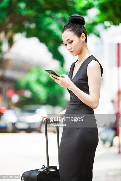 Young Asian Businesswoman Waiting For Her Carpool To Airport