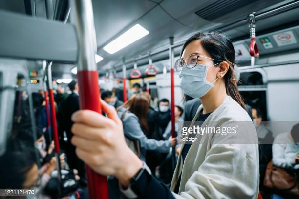 young asian businesswoman with protective face mask holding hand rail commuting in the city riding on a crowded subway in rush hour during the outbreak of covid-19 health crisis - state of emergency stock pictures, royalty-free photos & images