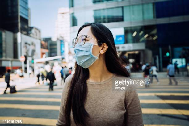 young asian businesswoman with protective face mask to protect and prevent from the spread of viruses during the coronavirus health crisis, commuting to work in downtown district in the city - stress coronavirus stock pictures, royalty-free photos & images