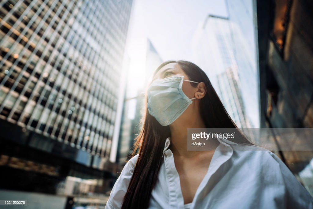 Young Asian businesswoman with protective face mask to protect and prevent from the spread of viruses during the coronavirus health crisis, standing in an energetic and prosperous downtown city street against corporate skyscrapers : Stockfoto