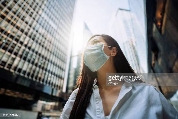 young asian businesswoman with protective face mask to protect and prevent from the spread of viruses during the coronavirus health crisis, standing in an energetic and prosperous downtown city street against corporate skyscrapers - パンデミック ストックフォトと画像