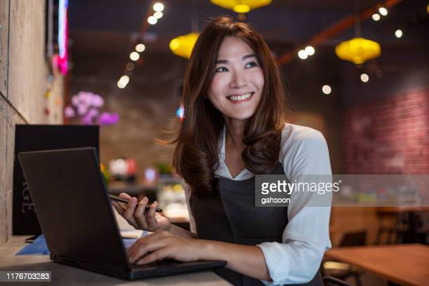 young asian cafe owner having some ideas for her business plan - franchising stock pictures, royalty-free photos & images