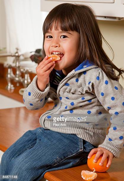 Young Asian child eating a clementine