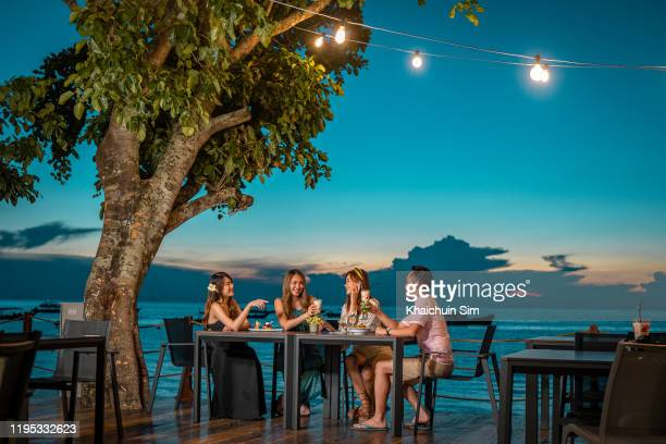 3 young asian chinese female and 1 young asian chinese guy dining at restaurant by the sea - medium group of people stock pictures, royalty-free photos & images