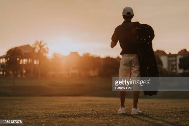 young asian chinese man golfer looking at sunset while carrying his golf equipment at golf course - twilight stock pictures, royalty-free photos & images