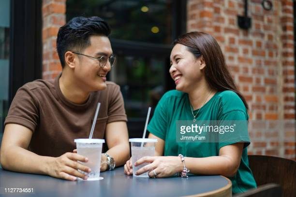 young asian couple chatting at a outdoor café, display affection for each other. - southeast stock pictures, royalty-free photos & images