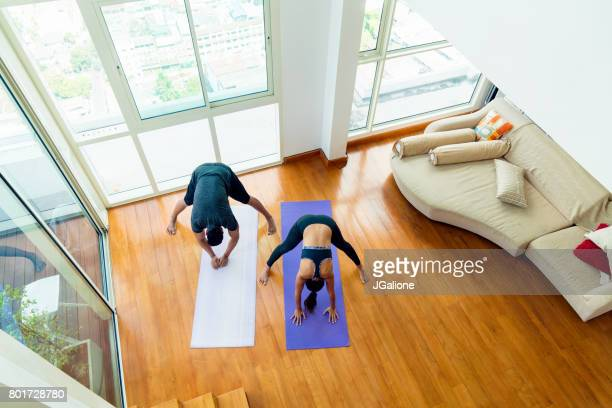 Young asian couple doing yoga at home