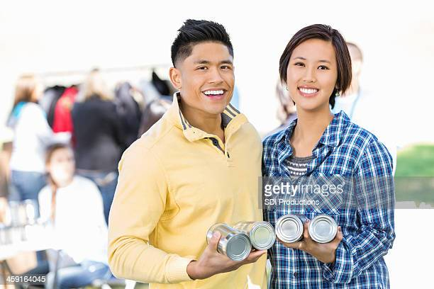 Young Asian couple donating food together at donation drive