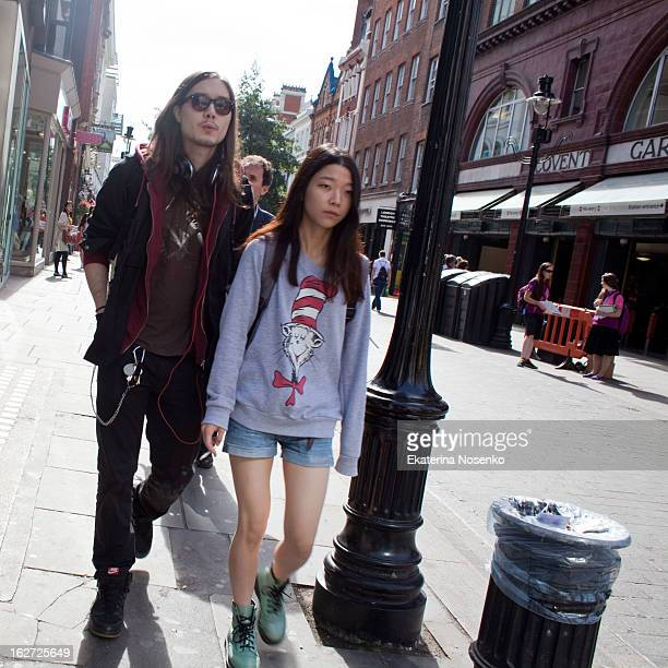 Young Asian couple dressed in accordance with the youth fashion is taking a stroll around Covent Garden, London. The girl is smoking. September 2012.