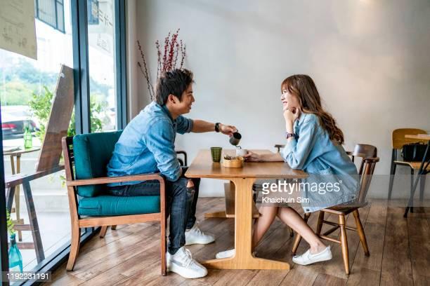 young asian couple drinking coffee at cafe coffee shop - citas románticas fotografías e imágenes de stock